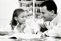 Father assisting his daughter with her homework