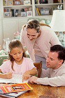 Parents helping their daughter study
