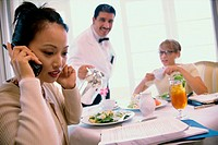 Businesswoman sitting in a restaurant talking on a mobile phone