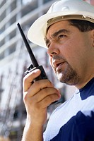 Low angle view of a foreman standing at a construction site talking on a walkie-talkie