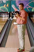 Portrait of a man holding a bowling ball in a bowling alley