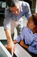 Businessman and a businesswoman working in front of a computer monitor