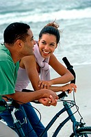 Young couple on bicycles at the beach
