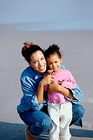 Portrait of a mother and her daughter playing together on the beach