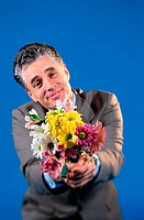 Portrait of a mid adult man holding a bouquet of flowers