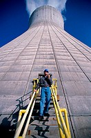 Low angle view of a man standing on a staircase of a smoke stack at a power plant