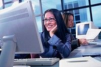 Businesswoman working on a computer smiling