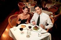 A couple in dinner wear celebrating their anniversary by eating in the restaurant