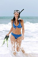 A happy lady in blue bikini walking back from snorkeling