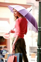 Back shot of a lady holding a purple umbrella and some paper bags