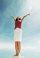 A lady standing on a high place looking at the sky with her hands up