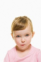 A three year old girl with blonde hair wearing  a pink top and hair pulled back,  looks away from the camera while deep in thought.