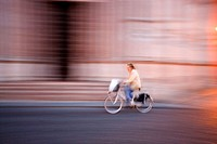Panning of a woman on bike in front of the pink marble baptistery of Parma. Emilia-Romagna, Italy