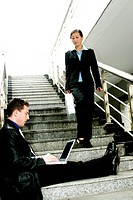 A man sitting on the stairs using laptop while a woman walking down the stairs.