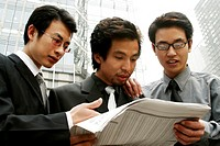 Three businessmen sharing a newspaper.