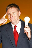 Businessman thinking while holding a light bulb.