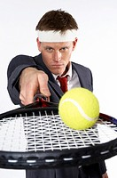 Businessman balancing a tennis ball on the racquet.