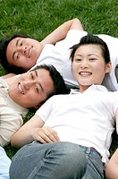 A lady lying on the grass together with her brothers.