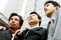 Low angle view of three businessmen standing in front of the building.