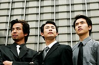 Three businessmen standing in front of the building.