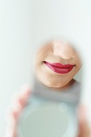 Reflection of a lady´s lips with red lipstick in a compact powder´s mirror.