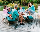 Three Generational Family Sit on Decking in Their Garden, Talking and Laughing