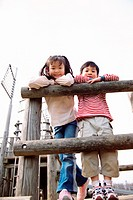 Young Girl and Boy Leaning Against a Wooden Fence on an Adventure Playground
