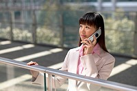 Businesswoman Standing by a Railing and Using a Mobile Phone