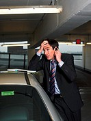 Businessman Standing by His Car and Using His Mobile Phone