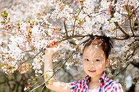 Portrait of a Young Girl Standing Next to Cherry Blossom