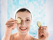 Woman With a Facial Pack Putting Slcies of Cucumbers on Her Eyes