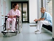 Young female doctor sitting by female patient in wheelchair