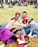 Group of friends embracing on grass, laughing