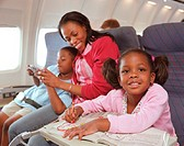 Family relaxing on aeroplane, girl (3-5) colouring, smiling