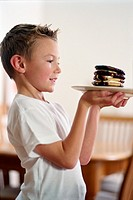 Boy (5-7) holding plate of chocolate covered pancakes, side view