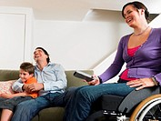Couple relaxing in living room with son (7-9) woman sitting in wheelchair, smiling