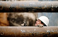 Construction worker in trench between pipes