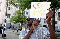 A senior citizen man holds a sign saying 'We need Jobs' as a protest at a parade. St. Louis, Missouri. USA