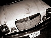 A Vintage Mercedes hood is captured at night. The hood of the car is worn, yet still has elegent details. The vintage nature of the car give it a time...