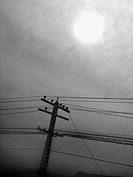 Powerlines and a Telephone Pole are silhouetted against a cloudy sky where the sun barely shines through. The effect is cosmic, and captures the feeli...