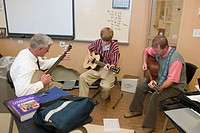 A student and two of his teachers gather to play instruments during an activity period during the school day