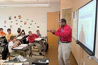 A black instructor teaches French to a class of students using a 'smart board' or electronic black board