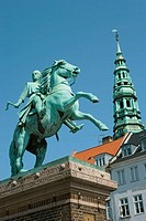 Equestrian statue of Bishop Absalon (1128-1201) in Hojbro Plads. Spire of Nikolaj Kirke background, Copenhagen, Denmark