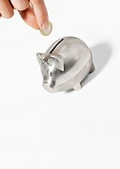 Hand inserting coin into piggy bank