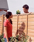 Man and woman talking over garden fence