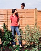 Man looking over fence at woman