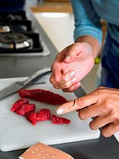 Woman in kitchen with cut on her finger