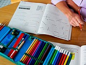 Woman with exercise books and pencil case