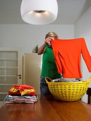 Woman folding clothes whilst on mobile phone