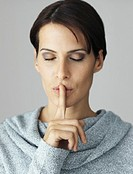 Woman with eyes closed and finger over lips